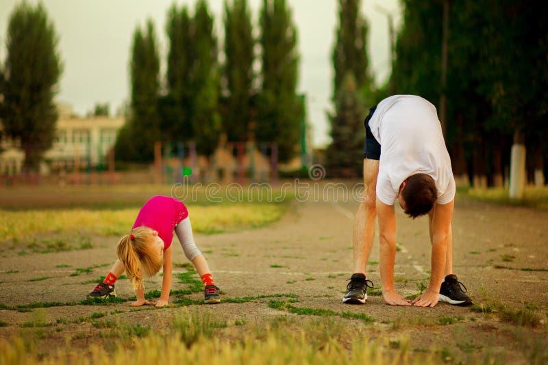 O pai novo atl?tico e a filha pequena fazem exerc?cios no est?dio foto de stock royalty free