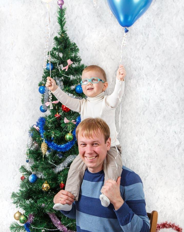 O pai novo com o menino engraçado no seu empurra perto do abeto do ano novo foto de stock