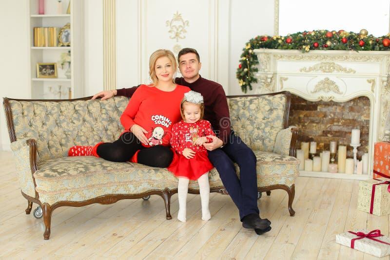 O pai novo e a mãe grávida que sentam-se com a filha pequena no sofá próximo decoraram a chaminé foto de stock