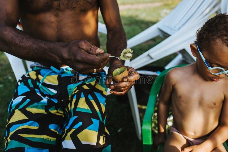 O pai preto oferece a seu filho um fruto de quivi e rejeita foto de stock