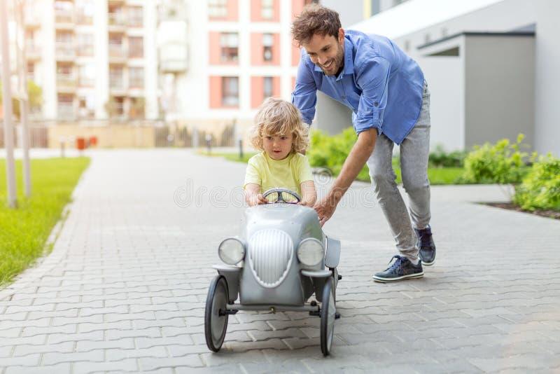 O pai que ajuda seu filho a conduzir um brinquedo vende de porta em porta o carro fotografia de stock royalty free