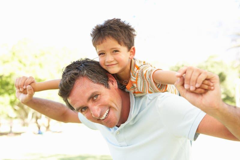 O pai que dá o passeio do filho suporta sobre no parque
