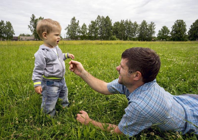 O pai que encontra-se em seu estômago agrada o filho 1 3 anos com ramo fotos de stock royalty free