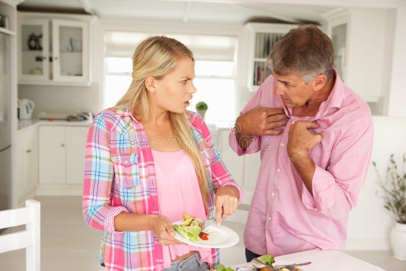 O pai que faz a filha adolescente faz tarefas em casa imagem de stock royalty free