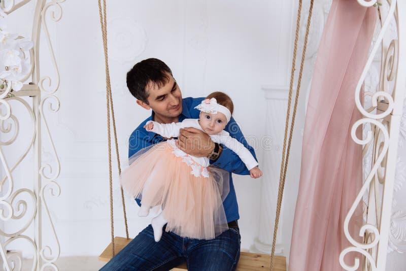 O pai rola sua menina Olha com interesse suas reação e emoções Uma menina está montando em um balanço imagens de stock royalty free
