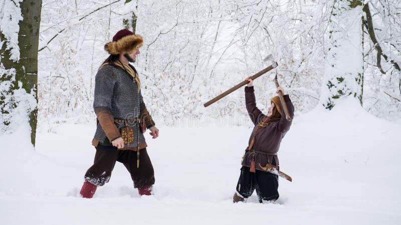 O pai viquingue ensina seu filho para lutar, realizando no machado de mãos imagem de stock