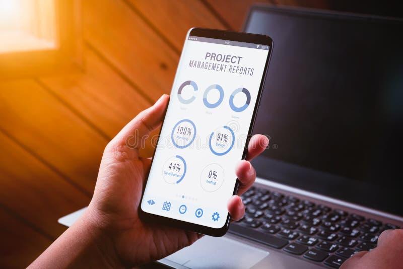 O painel da gestão do projeto relata o conceito da analítica dos dados Feche acima da mulher de negócio nova que guarda o telefon fotografia de stock