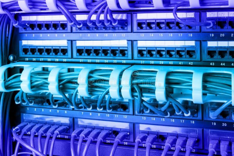 O painel, o interruptor e o Internet da rede cabografam no centro de dados Interruptor preto e cabos ethernet azuis, conceito do  foto de stock