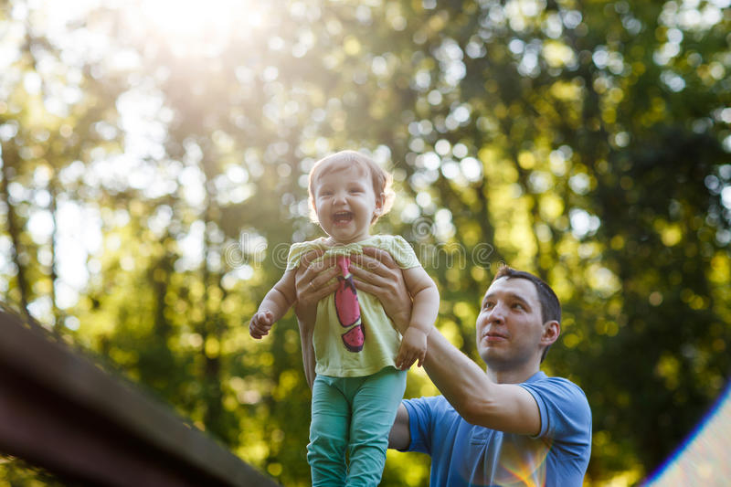 O paizinho apoia a menina que está na ponte no parque fotografia de stock royalty free