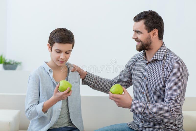 O paizinho bonito está ensinando a sua criança o estilo de vida saudável foto de stock
