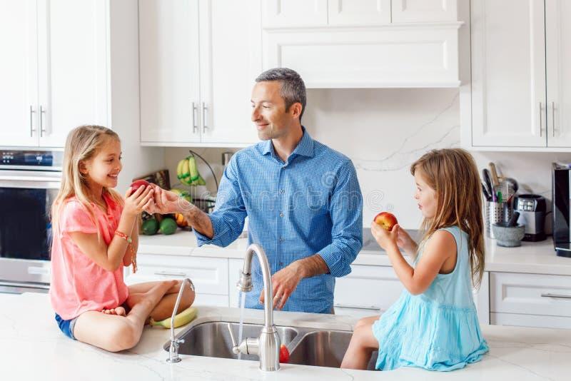 O paizinho caucasiano do pai dá a crianças filhas frutos frescos para comer imagens de stock