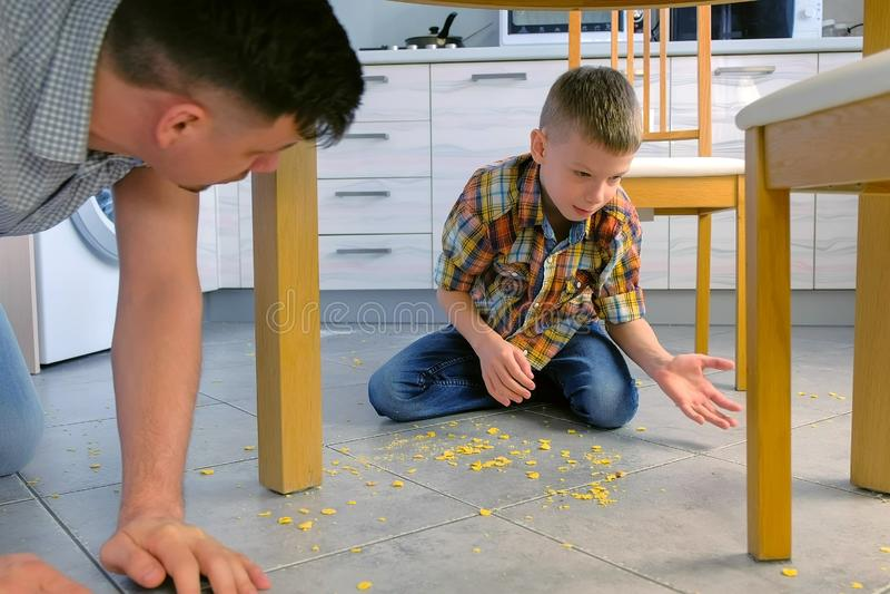 O paizinho discute seu filho para o alimento dispersado no assoalho da cozinha e fá-lo limpar Acima flocos de milho limpos fora d fotografia de stock