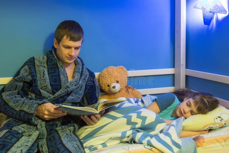 O paizinho diz a filha de sono uma história de horas de dormir fotos de stock royalty free