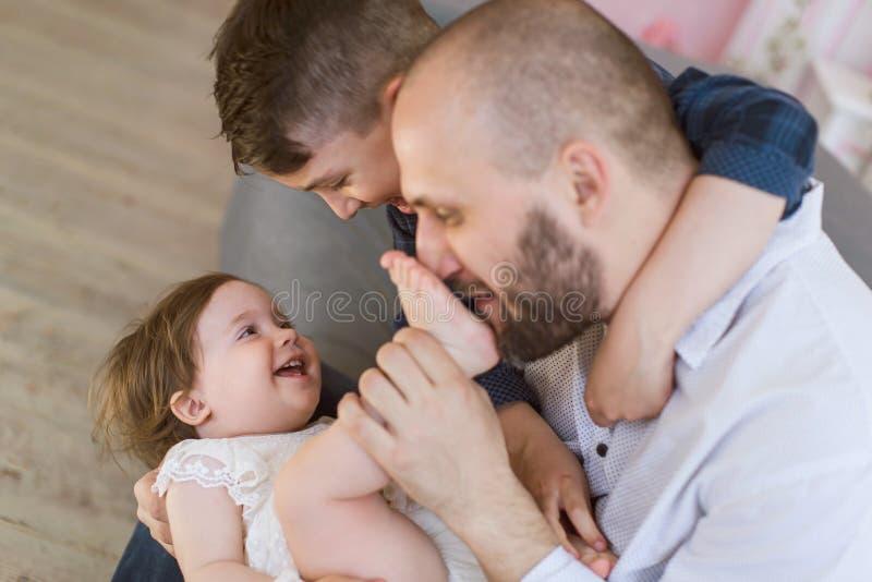 O paizinho e duas crianças têm um divertimento em casa foto de stock royalty free