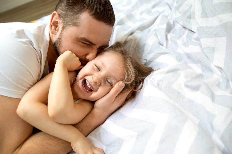 O paizinho e a filha têm o divertimento em casa na cama Dia do `s do pai fotos de stock royalty free