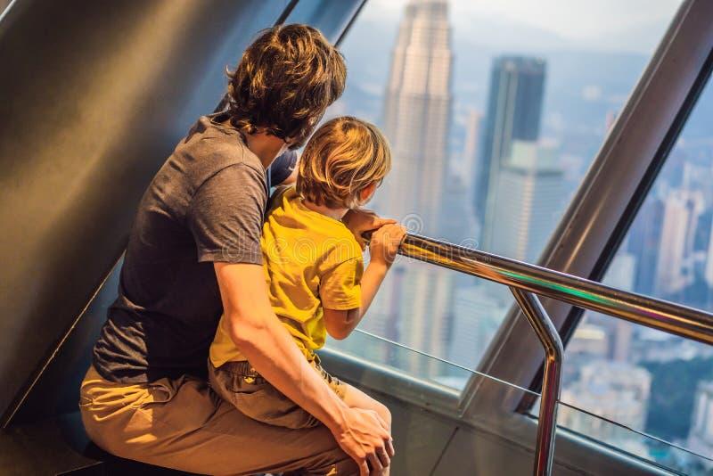 O paizinho e o filho estão olhando a arquitetura da cidade de Kuala Lumpur Vista panorâmica da noite da skyline da cidade de Kual fotografia de stock royalty free