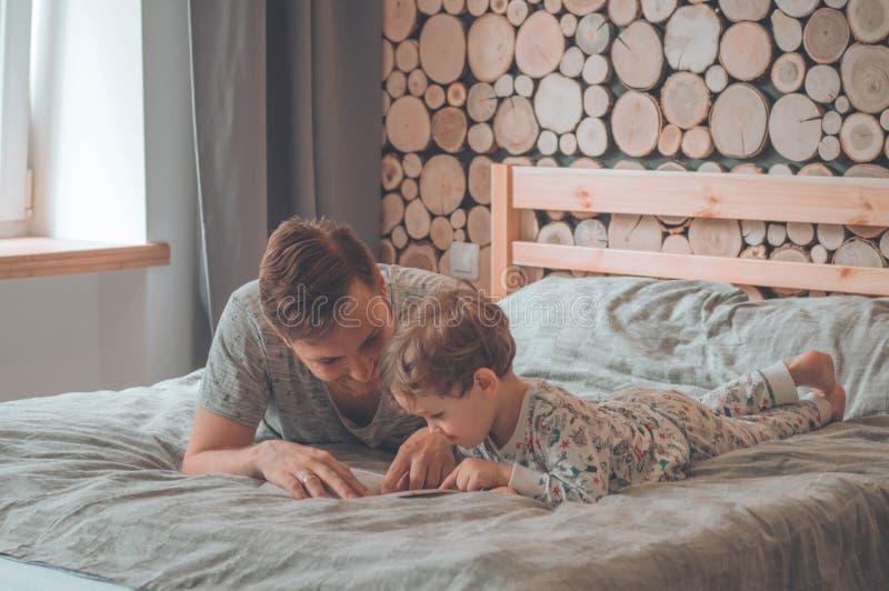 O paizinho e o filho leram um livro junto, o sorriso e o aperto Feriado e unidade da fam?lia Dia de pai feliz foto de stock
