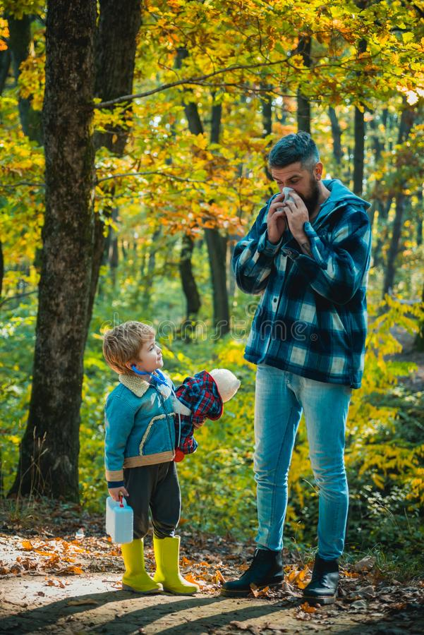 O paizinho e o filho no outono estacionam o riso do jogo Mostrando o pai doente que espirra no parque do outono Esta??o de gripe  imagem de stock