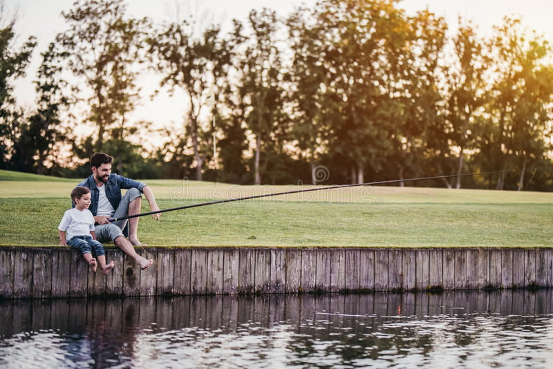 O paizinho e o filho estão pescando imagem de stock royalty free