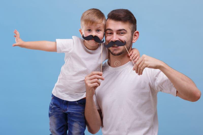 O paizinho e seu filho estão estando de lado a lado em um fundo azul Front View imagens de stock