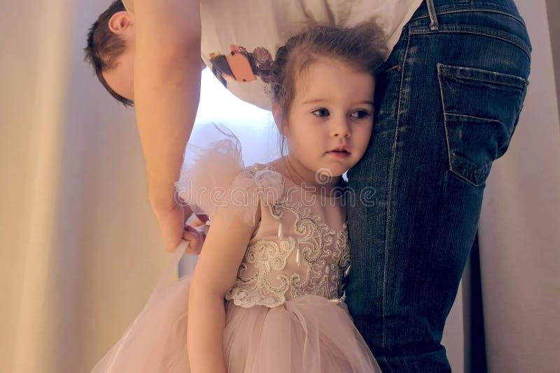 O paizinho está amarrando e ajuda-o a pôr sobre o vestido sua filha bonito Menina no vestido bonito fotos de stock royalty free