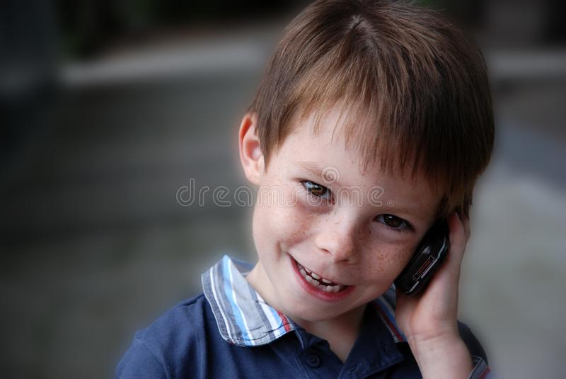 O paizinho está chamando, menino feliz da criança com telefone celular imagens de stock