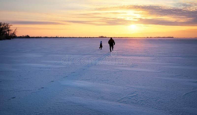 O paizinho está correndo para sua filha em um rio congelado no por do sol imagem de stock royalty free