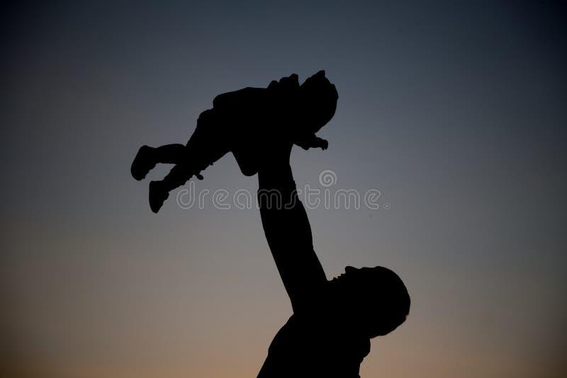 O paizinho feliz joga o bebê no por do sol fotos de stock royalty free