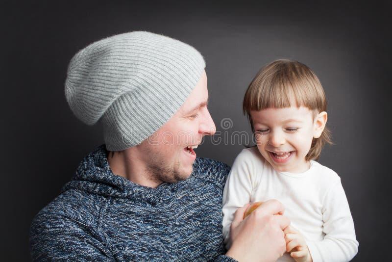 O paizinho joga com um filho pequeno bonito, sentando-se em suas mãos em um fundo preto no estúdio Diverte-o com Apple e eles bot foto de stock royalty free