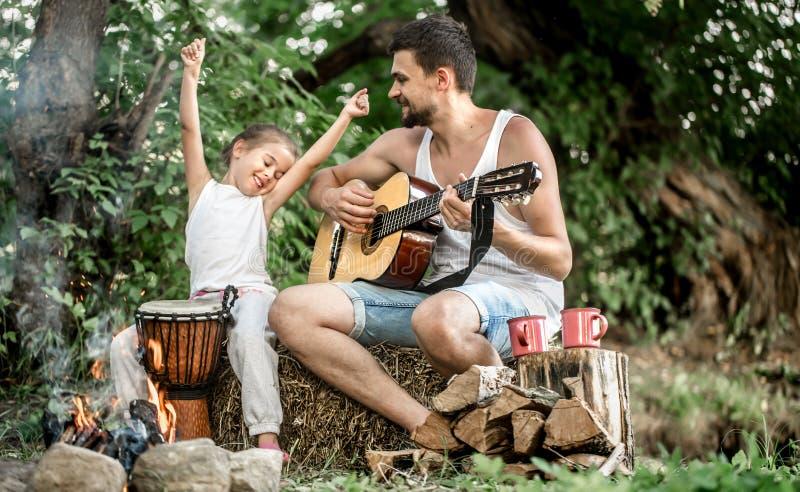 O paizinho joga a guitarra, filha na natureza fotos de stock royalty free