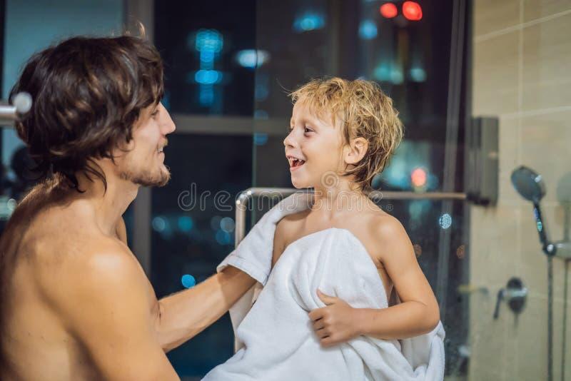 O paizinho limpa seu filho com uma toalha após um chuveiro na noite antes de ir dormir no fundo de uma janela com um panorâmico imagem de stock royalty free