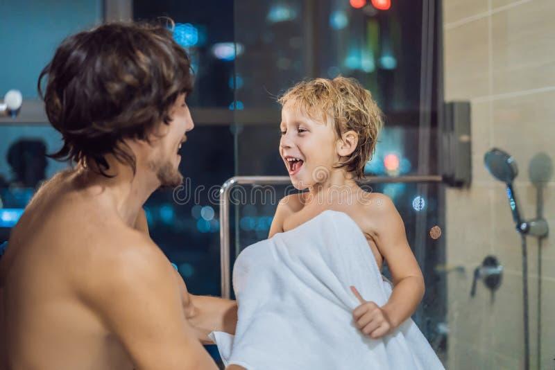 O paizinho limpa seu filho com uma toalha após um chuveiro no bef de nivelamento foto de stock