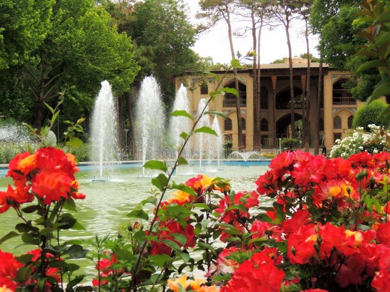 O palácio vermelho de florescência de Isfahan Hasht Behesht floresce pela fonte fotos de stock royalty free