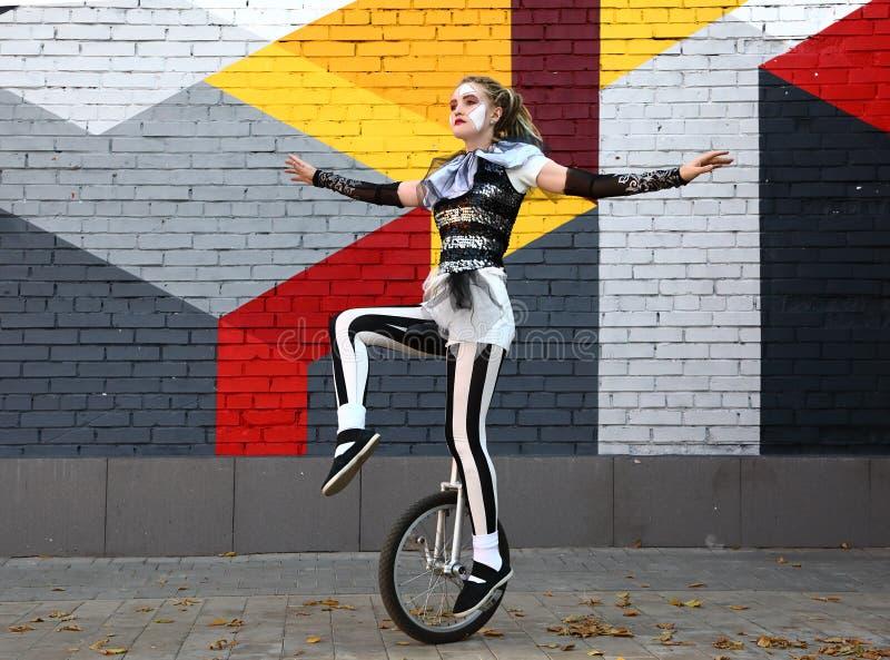 O palhaço da menina monta um unicycle fotos de stock