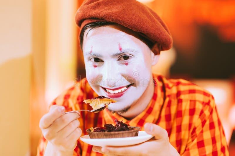 O palhaço está comendo um bolo em um café e sua cara está gralhando fotografia de stock royalty free