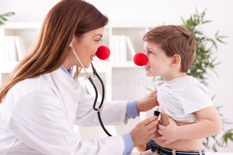 O palhaço fêmea adorável de sorriso do doutor escuta coração paciente fotos de stock royalty free
