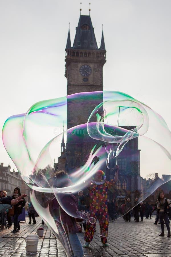 O palhaço faz bolhas grandes na praça da cidade velha Praga fotografia de stock