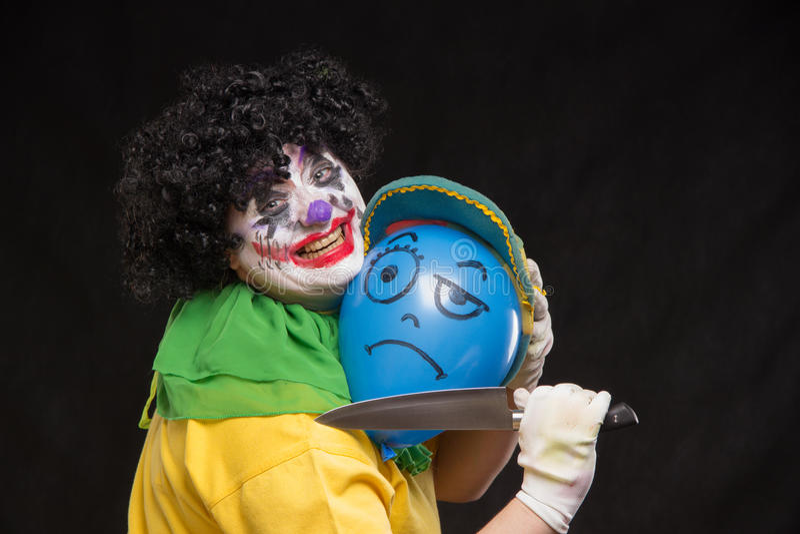 O palhaço feio irritado quer matar um balão no tampão imagem de stock royalty free