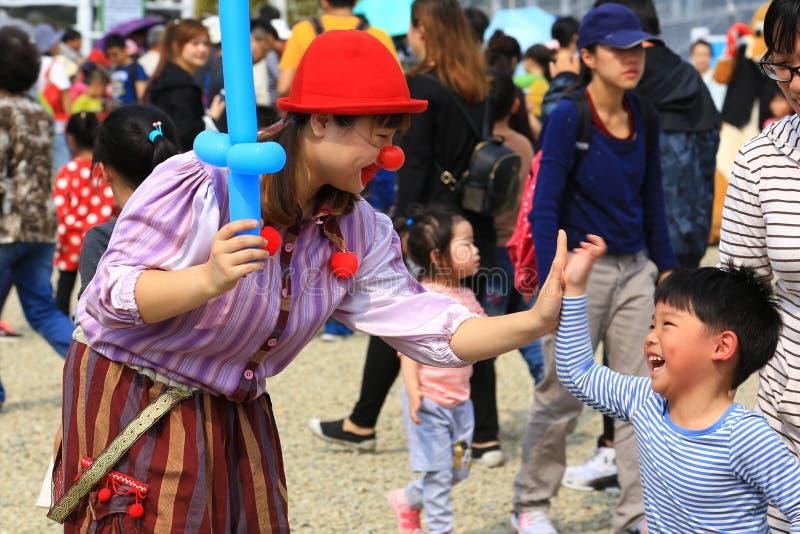 O palhaço Girl está dando um alto-Cinco a Little Boy em uma feira da cidade fotos de stock royalty free