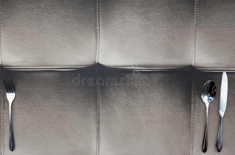 O pano feito do couro do búfalo, uma tabela em um restaurante americano Faca, forquilha, encontrando-se no projeto de couro da to imagens de stock royalty free