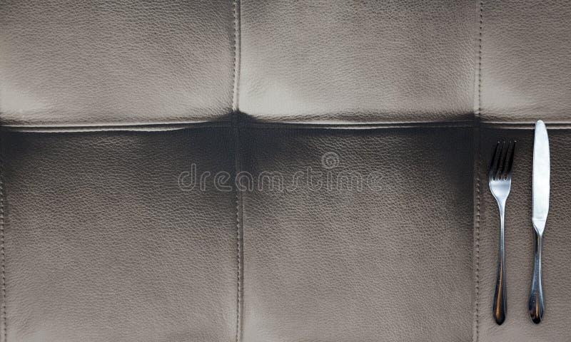O pano feito do couro do búfalo, uma tabela em um restaurante americano Faca, forquilha, encontrando-se no projeto de couro da to fotografia de stock royalty free