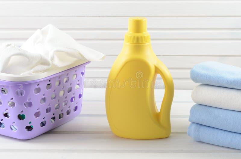 O pano sujo em uma cesta de lavanderia roxa plástica, limpa clo dobrados fotografia de stock