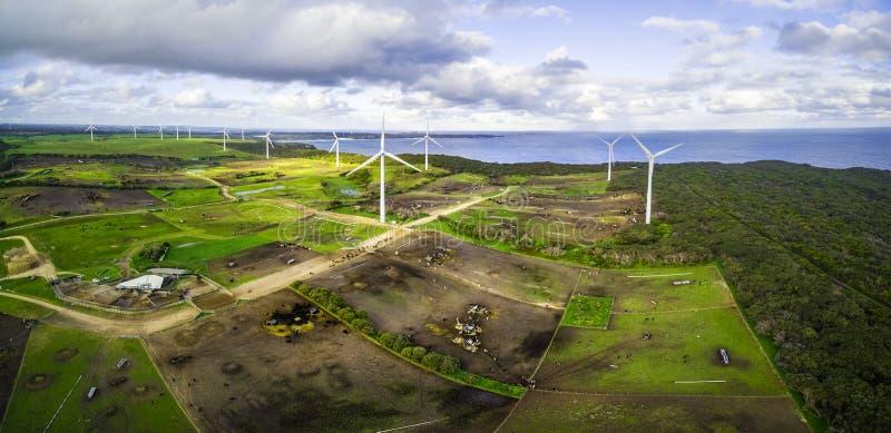 O panorama aéreo de nuvens tormentosos acima das turbinas eólicas e os pastos no oceano suportam imagens de stock royalty free