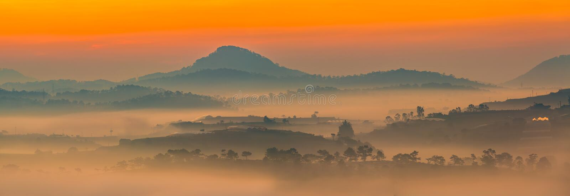 O panorama bonito da manhã ajardina com a névoa através das montanhas imagens de stock