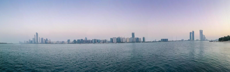 O panorama bonito disparou de torres e de praia da skyline da cidade de Abu Dhabi no por do sol fotos de stock royalty free