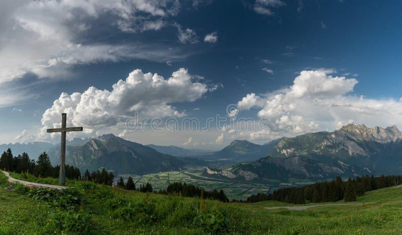 O panorama da montanha com uma vista lindo dos cumes e os vales suíços e uma cimeira cruzam-se fotografia de stock royalty free
