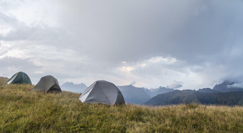 O panorama das montanhas, em um esclarecimento, lá é três barracas imagem de stock royalty free