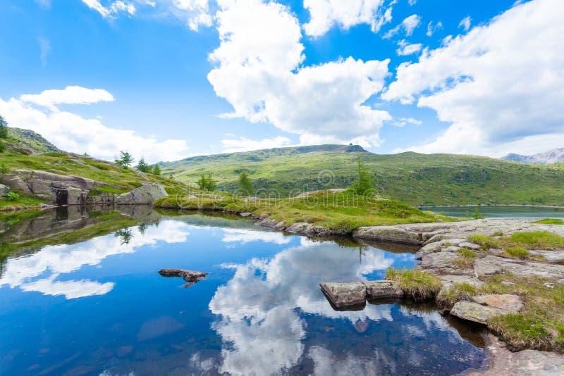 O panorama italiano da montanha, nuvens refletiu no lago alpino fotos de stock