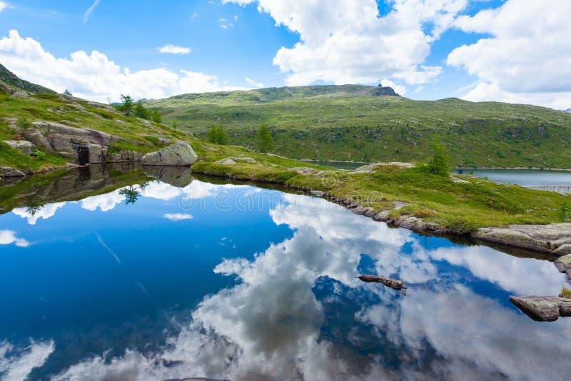 O panorama italiano da montanha, nuvens refletiu no lago alpino foto de stock