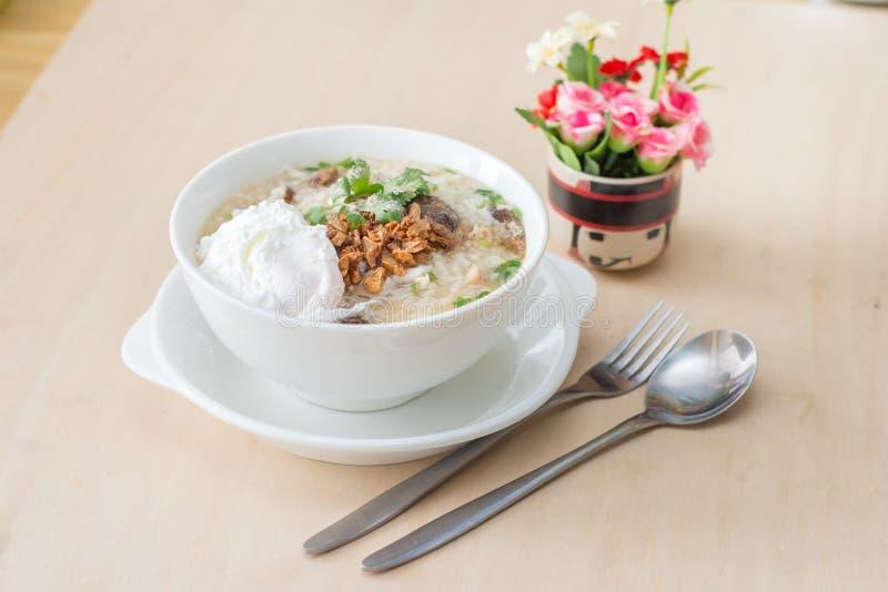 O papa de aveia do arroz com alho e o ovo tomam o café da manhã na bacia branca na tabela de madeira imagens de stock